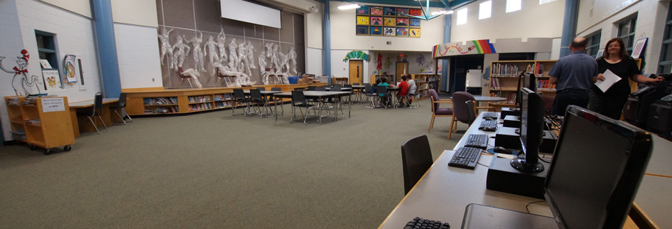 Tables, chairs, books in the Learning Commons area